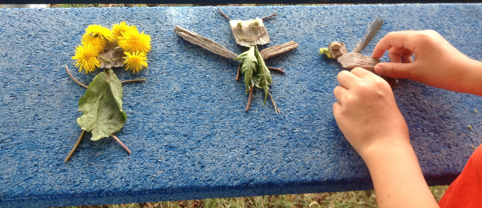 Hands seen puting together sticks and flowers into small dolls